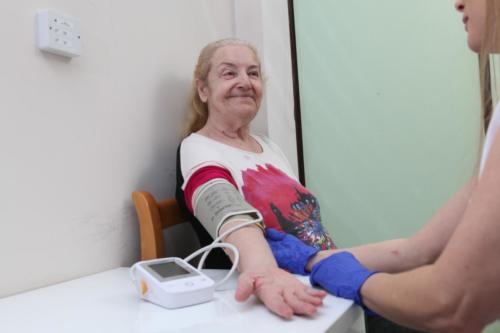 zdjęcie troskliwa pielęgniarka monitoruje stan zdrowia mieszkanki domu poprzez zmierzenie ciśnienia aparatem naramiennym.